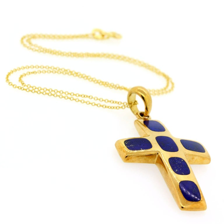 "A beautiful 1970s Italian 18KT yellow gold cross with six cushion shape inlaid Lapis Lazuli stones. The cross is suspended from a 14KT yellow gold 16 inch box link chain, and measures 2 inches high by 1 1/8 inches wide.  The bail is stamped ""750 PV"