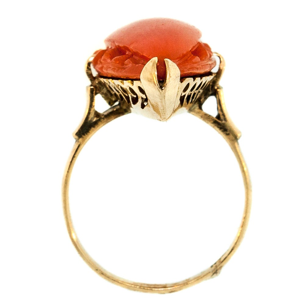 Marquise Shape Coral is set in a beautifully crafted 14 KT Yellow Gold band. The sunset red gemstone features carved engravings—a detail that is reminiscent of the piece itself: natural yet eloquent. Circa 1910, this piece measures at 1 1/4 inches