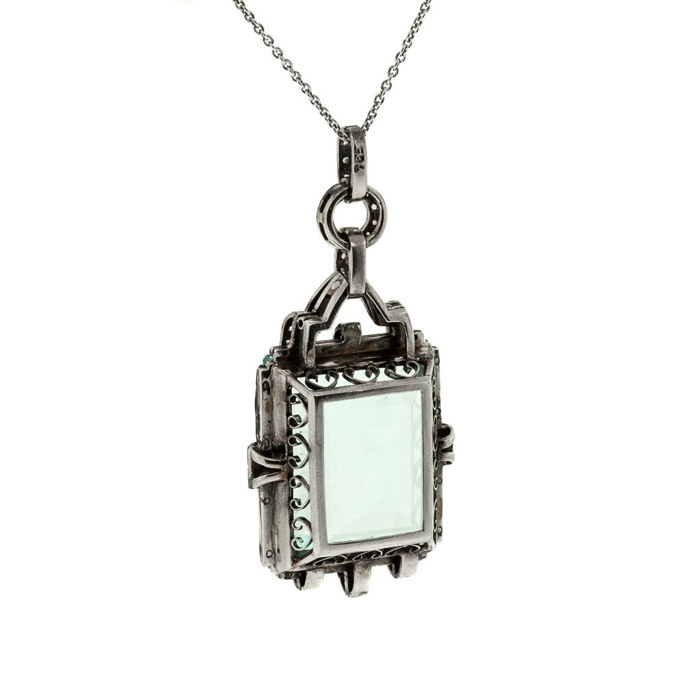 This beautiful Art Deco Aquamarine pendant is set in platinum and accented with small Rose Cut Diamonds and black enamel borders. It hangs from a 18 inches long 14KT white gold cable link. It measures 2 inches long by 7/8 wide. Circa
