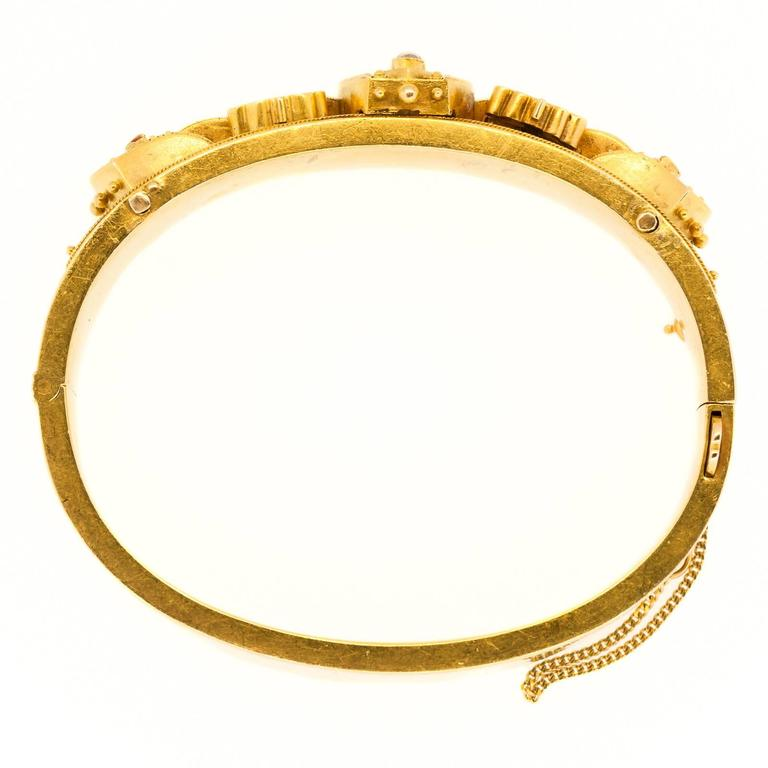 Circa 1890 14KT yellow gold barrel shaped bangle with wave sections and swirl design and accented with three natural pearls.