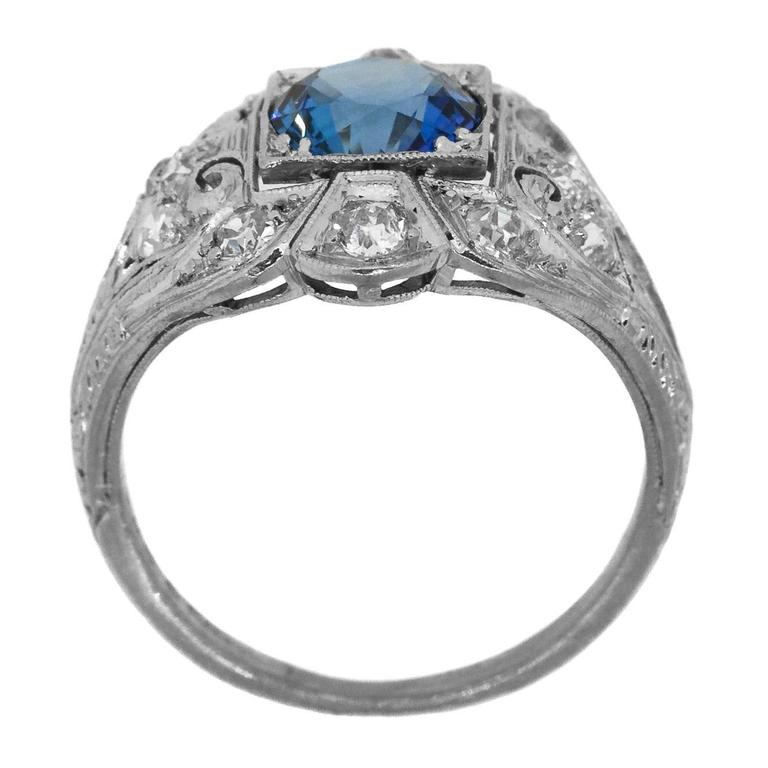 "Art Deco platinum ring featuring a Ceylon Sapphire surrounded by twelve Old Cut Diamonds, evaluated as I/J color – VS/SI clarity set in a beautiful platinum setting with swirl design and filigree, enhanced with a ""wheat"" engraving on the sides."