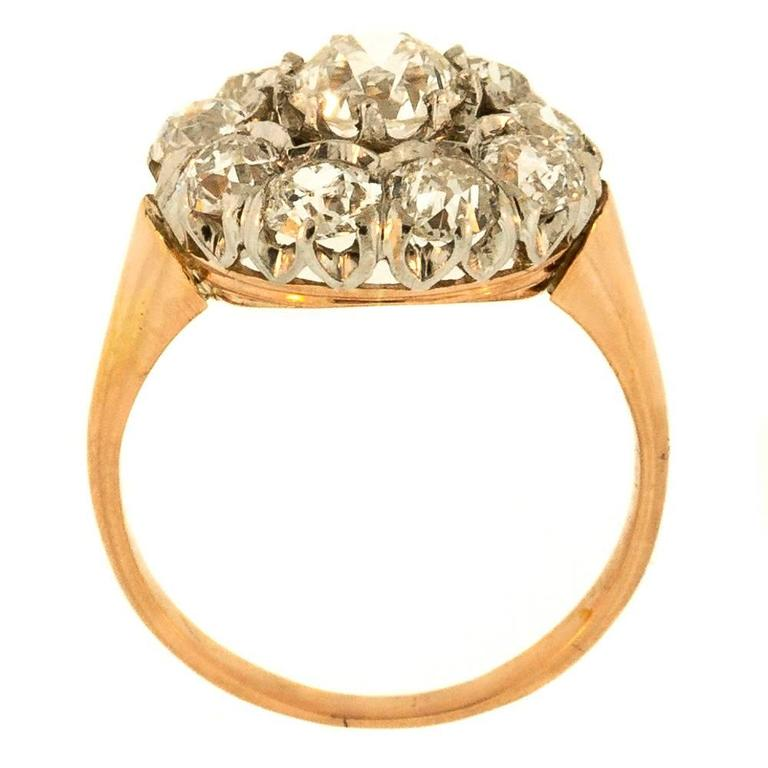 This antique diamond cluster ring is fabricated in 18KT rose gold and centers an Old European Cut Diamond, E.G.L. US H color – VS2 clarity. The center diamond is surrounded by nine Old European Cut Diamonds. The diamonds are all prong set in a