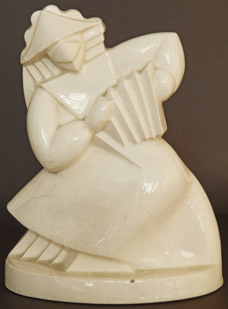 A classic example of Art Deco design heavily influenced by Cubism, this ceramic sculpture depicts a Chinese figure playing an accordian, with the creases of the instrument echoed in the robes of the figure, all enrobed in a creamy glaze with a