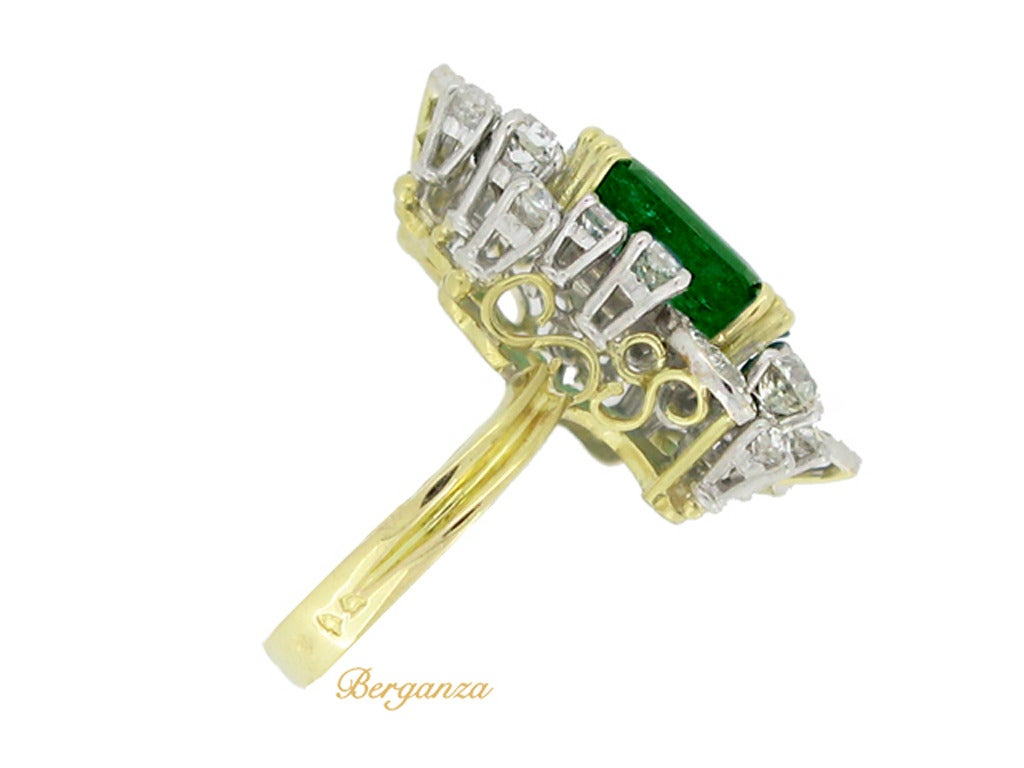 Emerald and diamond cluster ring. Set with a square emerald-cut natural Colombian emerald with no colour enhancement in an open back triple corner claw setting with an approximate weight of 4.78 carats, encircled by a cluster of twenty three round