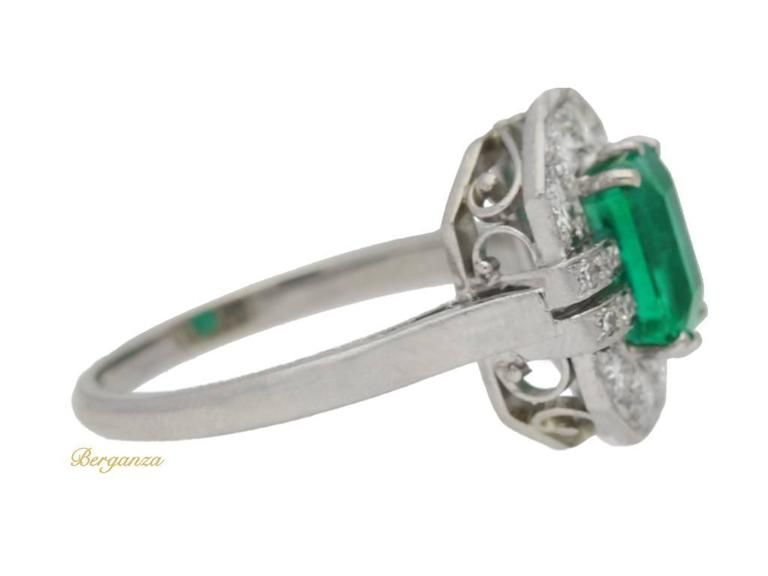 Art Deco emerald and diamond ring. Set with an octagonal emerald-cut natural Colombian emerald with no colour enhancement in an open back claw setting with an approximate weight of 1.38 carats, encircled by eight round old cut diamonds in open back