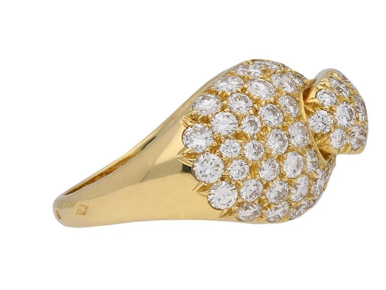 Diamond and yellow gold dress ring by Boucheron Paris. Set with a total of ninty one round brilliant cut diamonds of varying sizes in open back grain settings with an approximate combined weight of 3.70 carats, to a curving cluster with central