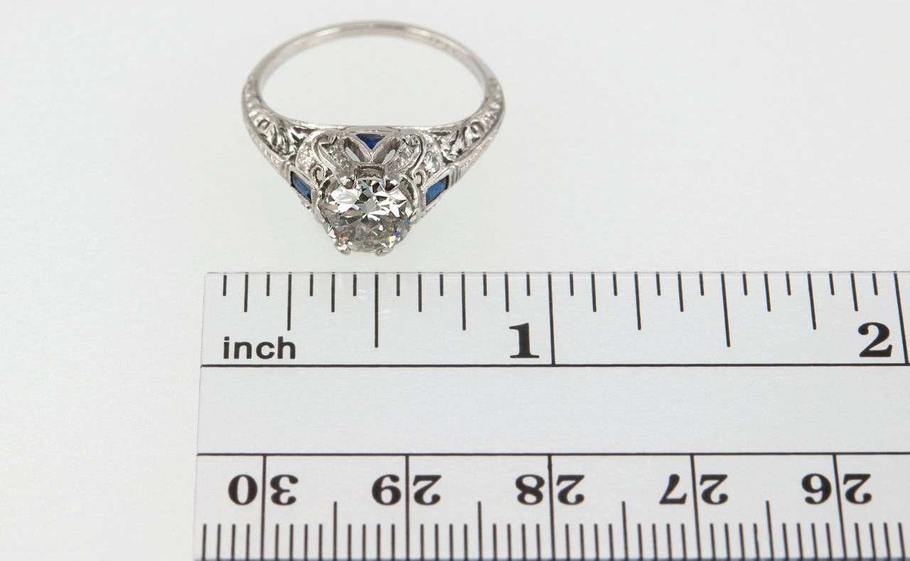 This beautiful Art Deco ring features a 1.04ct H-VS2 (EGL) diamond set in platinum accented by four small round diamonds and calibre cut sapphires with  lovely filigree and open-work. Circa 1920s.