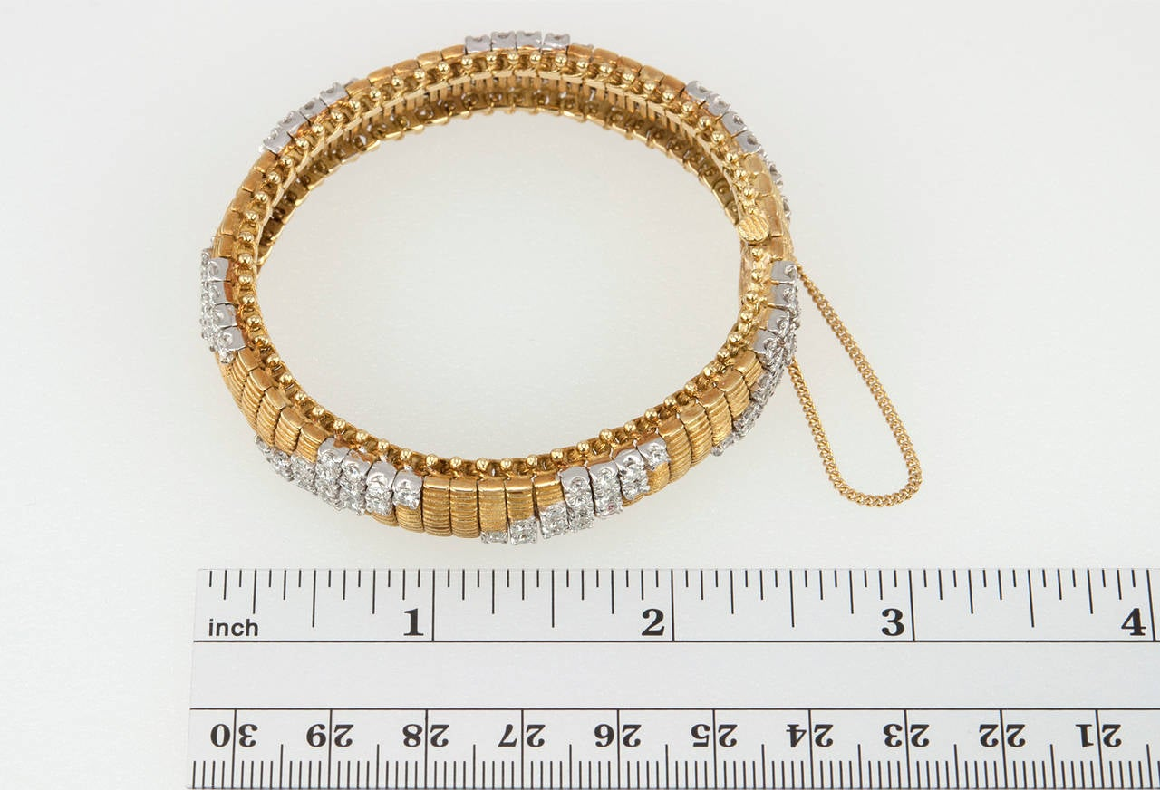 Flexible link bracelet with 112 diamonds in a repeating geometric pattern in 18 karat yellow gold with a safety chain. There are approximately 4.50 carats of total diamond weight in this bracelet. Marked T.L., circa 1960s.