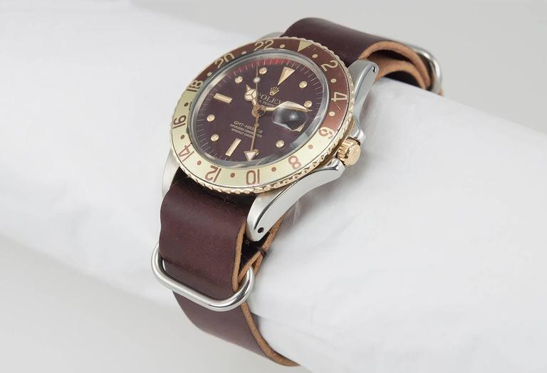 Rolex GMT 2-Tone wristwatch, reference 1675. This super collectable Rolex watch features a stainless steel case with a 18K yellow gold bezel with a brown and yellow aluminum bezel insert. It has an original period brown