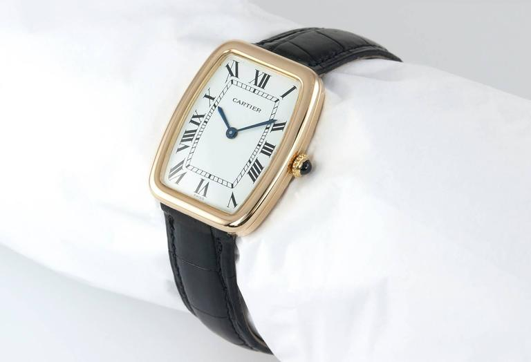"Cartier 18 karat yellow gold ""square incurvee"" wristwatch (as seen in the book, Le Temps de Cartier page 228).  This beautiful large Cartier watch features, a tradition white dial with black roman numerals, it has a glass crystal, small gold crown"