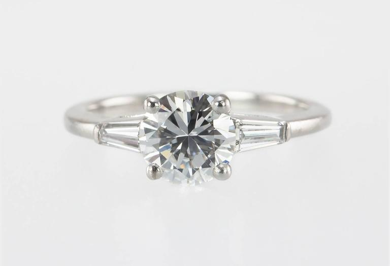 A classic and chic Cartier diamond and platinum engagement ring from circa 1950s.  This ring features a 1.00 carat round brilliant diamond that is H in color and VVS1 in clarity (per GIA certificate) and is flanked by two diamond baguettes each