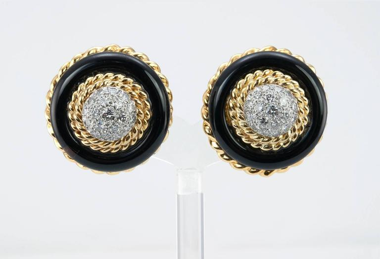 Van Cleef & Arpels NYC bold clip on earrings.  These chic vintage earrings from the 1960s feature 19 round brilliant cut diamonds in the a center dome shape (in each earring) surrounded by two rows of textured gold then surrounded by a onyx and