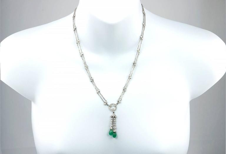 A stunning antique necklace from circa 1920s!  This long necklace features a double platinum link chain that alternates with bezel set diamonds leading down to the center drop of diamonds and 2 polished emeralds.  The 80 Old European Cut diamonds in