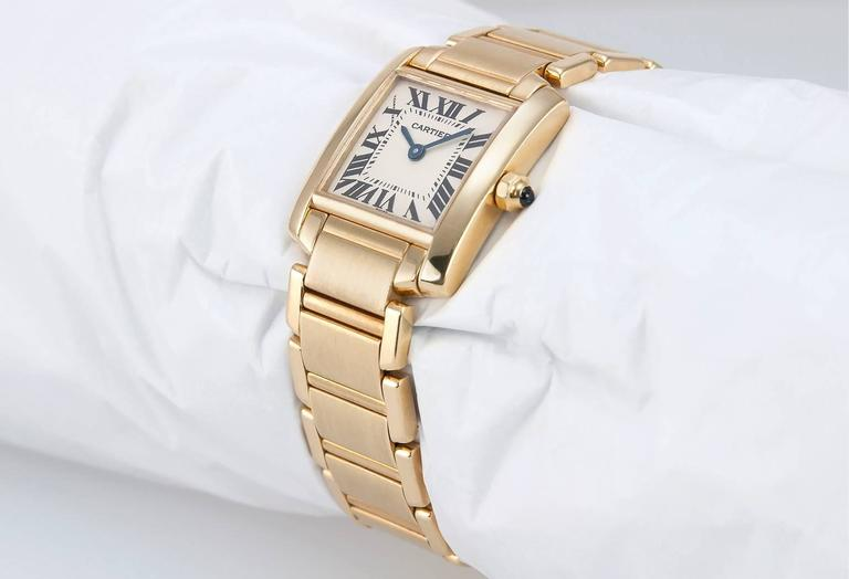 A Cartier Tank Francaise ladies wristwatch in 18 karat yellow gold, 25 mm x 20 mm in size. A Swiss made quartz watch with sapphire crystal, smooth bezel, white flat dial, blue steel sword hands, black Roman numeral hour markers, push/pull crown