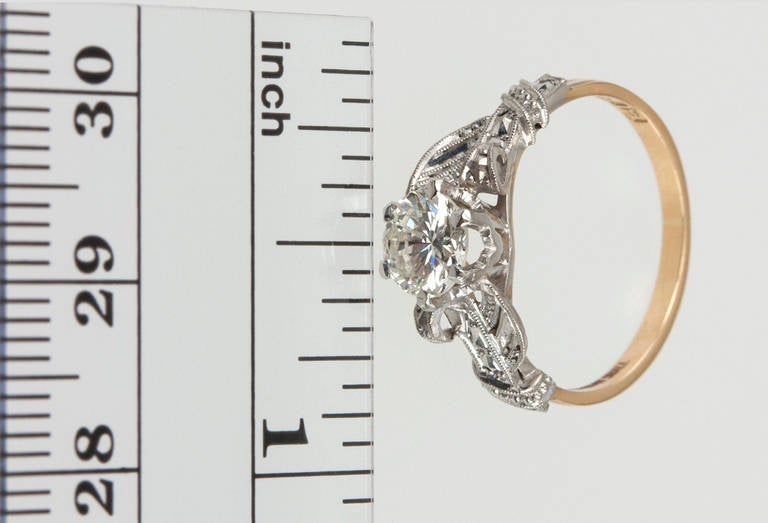 A beautiful Edwardian engagement ring featuring a 0.84ct I-SI2 diamond (EGL) and a gentle scrolling pattern accented with fine milegraining and pierced open work in platinum and 18k yellow gold, circa 1910s. 