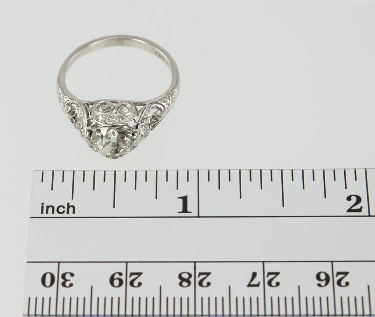 This is a beautiful and feminine Edwardian engagement ring which features a 1.31ct J-SI1 diamond (EGL) accented by nine small round diamond side stones with lovely filigree, open-work, and engraving. Circa 1915.  Currently a US size 6.25 and