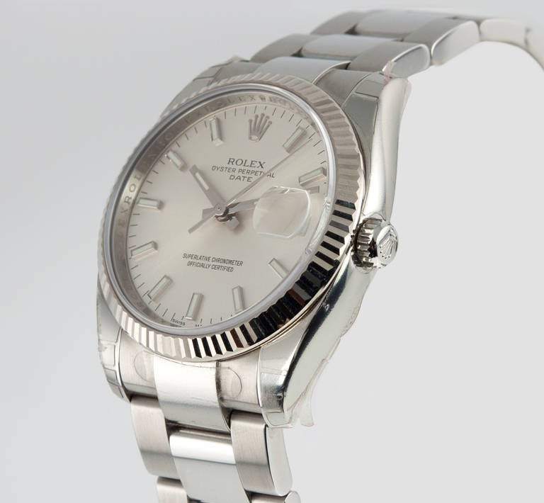Rolex stainless steel Date wristwatch, Ref. 115234, with an 18k white gold bezel. This is a 31-jewel self-winding movement watch with a case that measures 34mm with a silvered satin dial and scratch-resistant sapphire 
