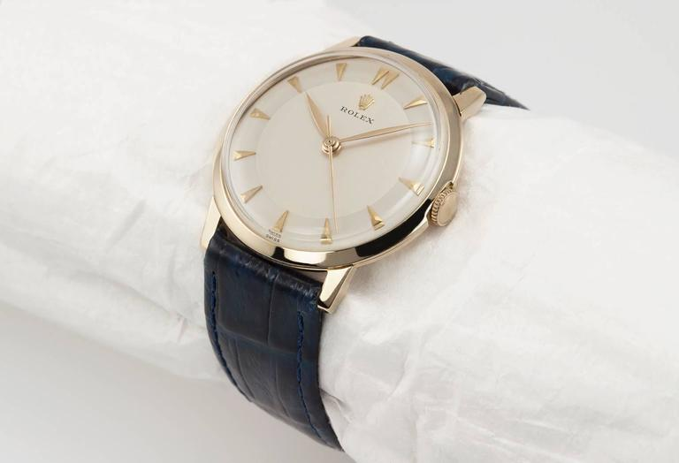 Rolex dress watch in 14 karat yellow gold, reference 0066. This 1960's Rolex watch is simple and chic. It has a 17 jewel mechanical movement, original dial, plastic crystal, with a new blue leather strap. Circa 1968. This case measures approximately