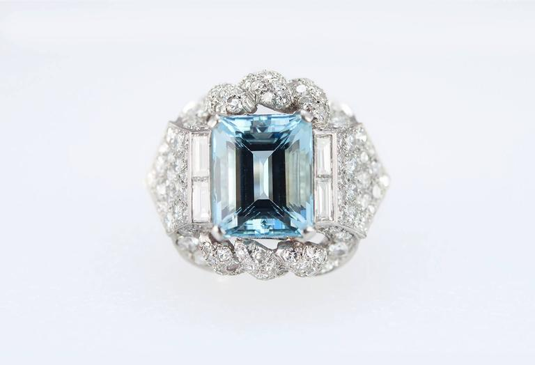 A beautiful 1960s platinum cocktail ring featuring a 5.45 carat aquamarine center surrounded by 4 baguette diamonds and an additional 128 round diamonds set throughout the mounting, approximately 3 carats in total diamond weight. The ring is