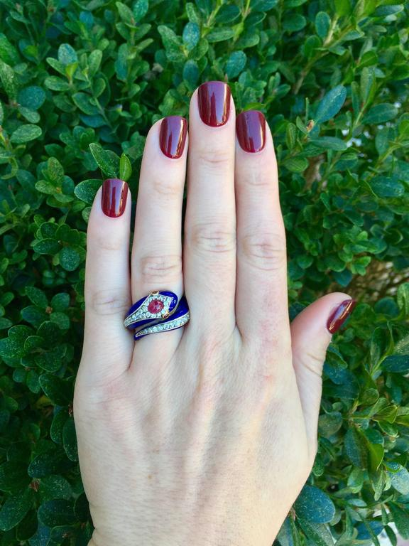 This vintage 18 karat yellow gold and platinum snake ring has beautiful dark blue enamel on its body.  37 old cut diamonds are set around the curved body, totaling approximately 1 carat in diamond weight.  A ruby cabochon is set on the snake head