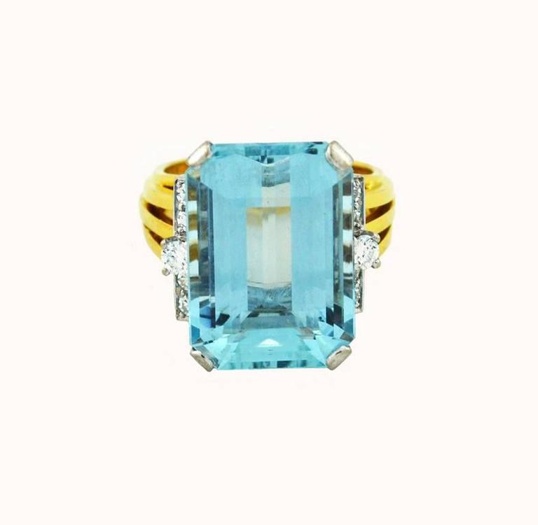 A fantastic, large scale cocktail ring from circa 1960 featuring a beautiful aquamarine.  This ring is crafted in 18 karat yellow gold and platinum with a maker's mark of S+F.    The aquamarine is approximately 13.80 carats with 10 round brilliant