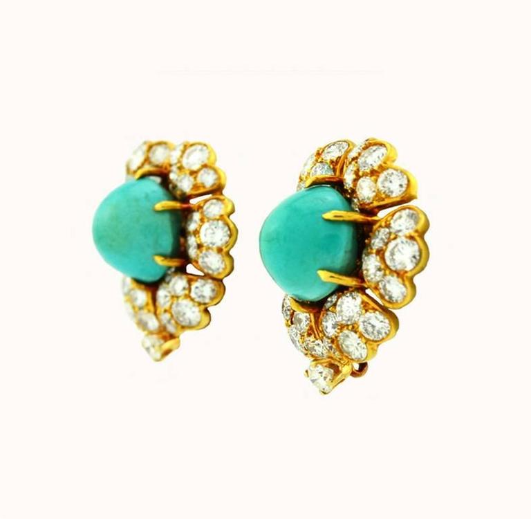 A beautiful pair of David Webb turquoise and diamond gold cluster earrings in 18 karat yellow gold.  These clip-on earrings feature 2 greenish-blue turquoise cabochon at the center of each earring and 74 round cut brilliant diamonds, which total
