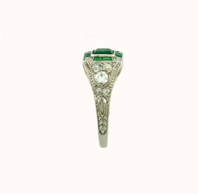 An Art Deco emerald and diamond platinum ring from circa 1920.    This beautiful ring features a 0.45 carat bright emerald center along with 6 calibre cut emeralds, which total approximately 0.27 carats. And further decorating the setting are 14 Old