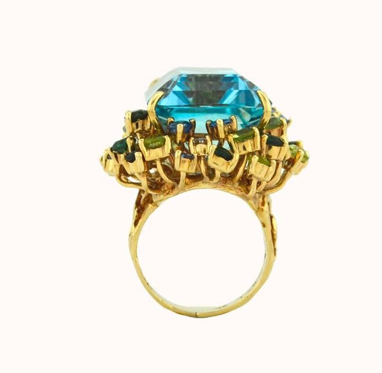 A fantastic 1960s aquamarine cocktail ring in 14 karat yellow gold.  This ring features a 35.50 carat Santa Maria aquamarine in a vibrant and beautiful blue hue.  Surrounding the aquamarine center are peridot, diamond and sapphire side stones.