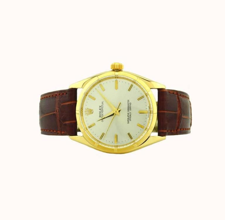 A classic Rolex Oyster Perpetual wristwatch in 14 karat yellow gold, reference 1003. This beautiful Rolex features a 14 karat yellow gold oyster case, a 14karat yellow gold engine turned bezel, plastic crystal, silvered satin original dial, with