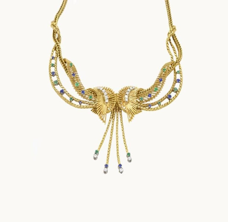 Chic retro 18k yellow necklace made by Carl Bucherer in the 1960s.  Set with 0.50 carat of diamonds along with sapphires and emeralds.  The necklace is 16.75 inches around.