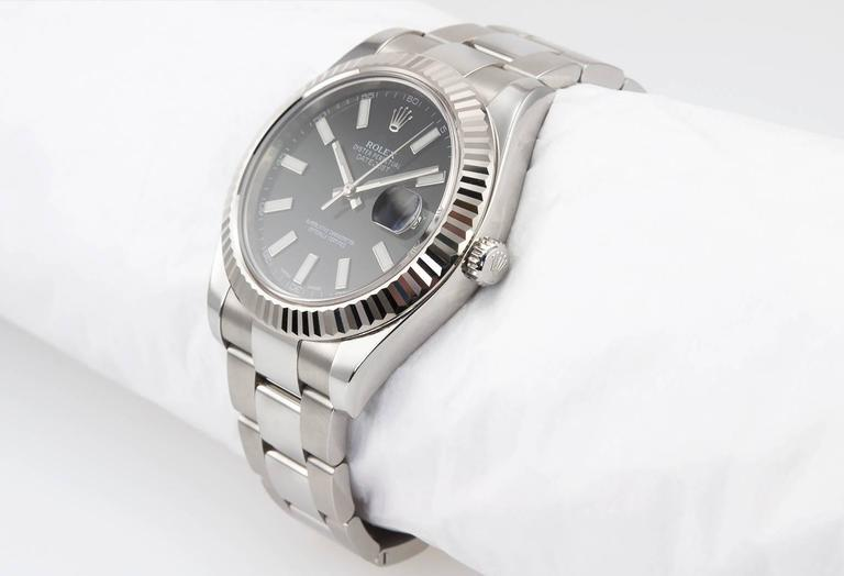 Rolex DateJust II wristwatch in stainless steel with a 18K white gold fluted bezel, reference 116334. This Rolex watch features a black dial with white stick markers, stainless steel Oyster bracelet, sapphire crystal, steel waterproof crown. The