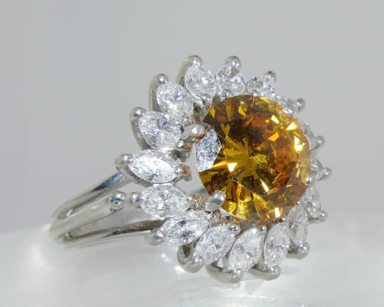 The center brilliant cut diamond displays a bright cognac color, it weighs 2.68 cts.  This diamond has been examined by the G.I.A. (Report No. 2430550), and is treated color.  The white marquis cut diamonds surrounding this stone weigh approximately