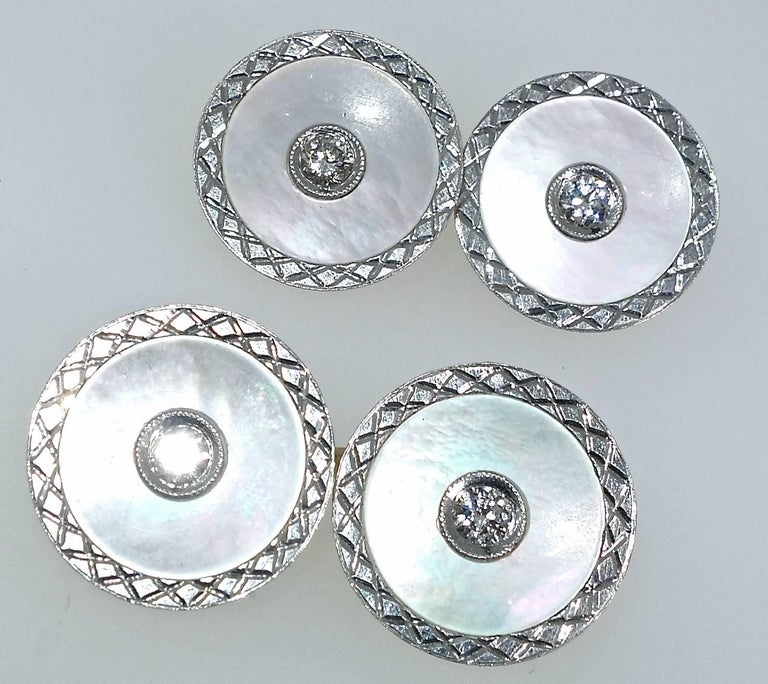Platinum cufflinks with engraved edges surrounding white mother of pearl  and a bead set diamond in the center and backed with gold.  There are .33 cts. total weight of the white European cut diamonds.  Early Art Deco.