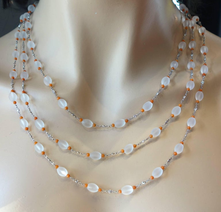 This long chain possesses frosted Rock Crystal interspersed with bright orange coral beads and diamonds.  The necklace is 67 inches long and can be worn a variety of lengths.  The diamonds are all round brilliant cut, near colorless and slightly