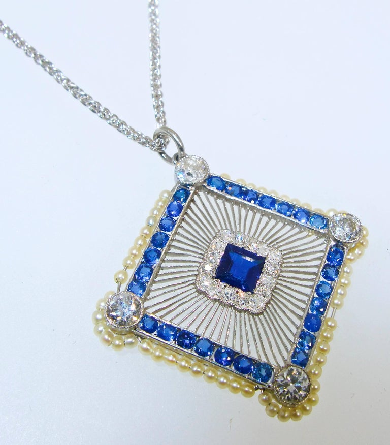 Circa 1915, Edwardian platinum pendant possessing just over .70 cts of small diamonds and 29 fine blue natural sapphires weighing totally just over 2.0 cts.  The pendant, which is bordered with natural small seed pearls, is .75 inches wide and 1.0