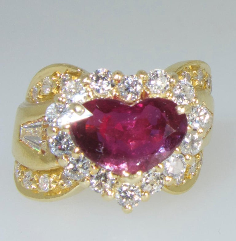 Fine natural bright red ruby heart surrounded by and accented with fine white diamonds.  The ruby is natural with a bright Burma like color.  It is estimated to weigh approximately 2 cts.  The white diamonds weigh approximately 1.3 cts and are all