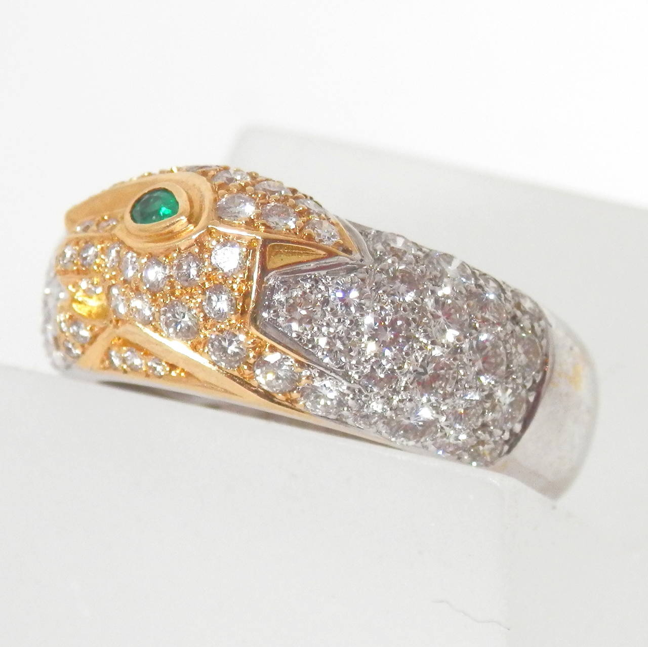 In 18K gold, an emerald eyed Panther in yellow gold is set off with a white gold diamond surround.  The ring is a size 6 1.2 and can be sized.  It is signed Cartier, numbered EO8573 and is dated 1996. The shank varies from 6.0 to 8.4 mm  It