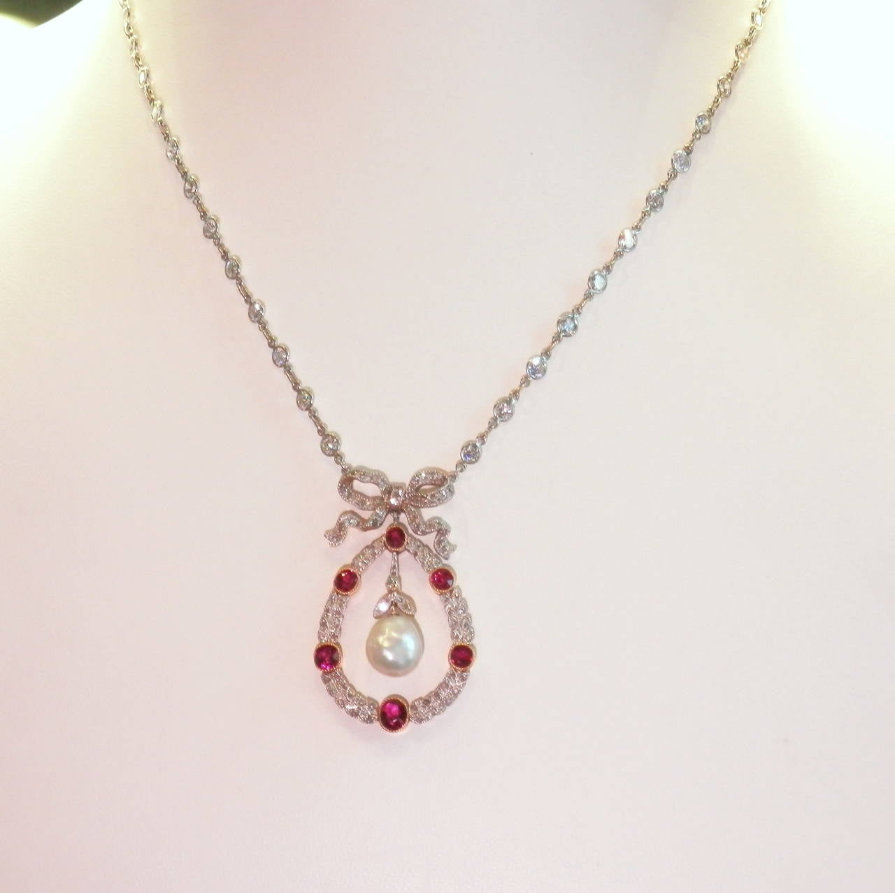 Platinum on gold pendant necklace with 1.50 cts. of natural unheated Burma rubies, 1.50 cts of diamonds and centering a natural 9.2 mm. pearl, the diamond chain in contemporary.