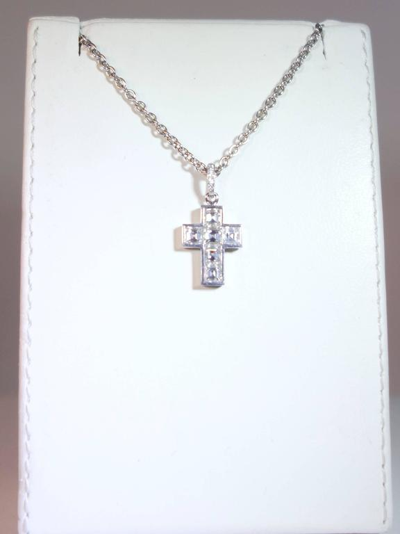 Six square cut fine diamonds all well matched and approx. (F) colorless and (VVS) very very slightly included.  Both the pendant and the chain are signed Cartier and numbered 868034.