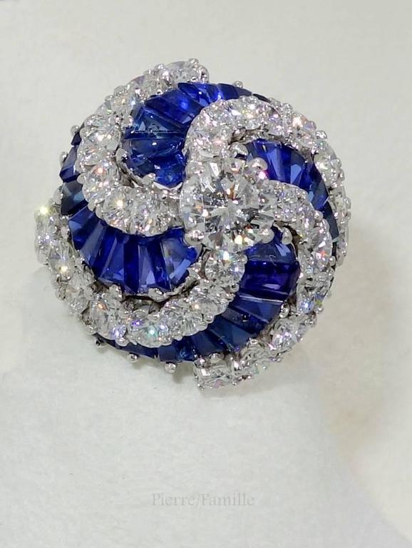 There are approximately 3.25 cts of fine diamonds all approximately F/G,VVS, (colorless to near colorless and very very slightly included).  The center diamond weighs approximately .75 cts.  There are 32 fancy cut fine blue sapphires weighing