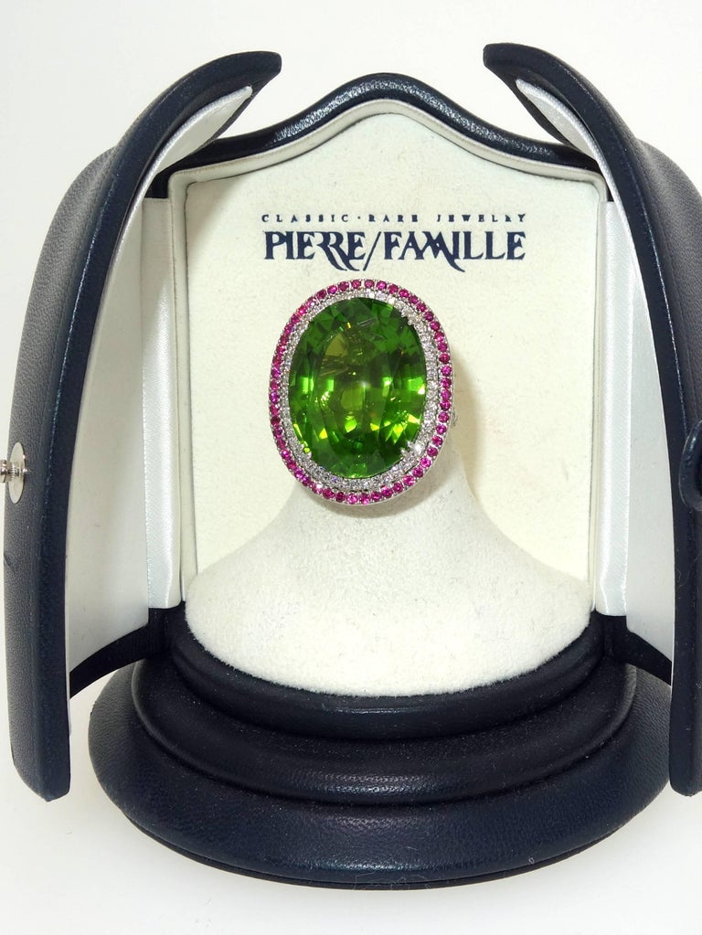 Fine bright green natural Peridot, probably Egyptian, handmade in platinum, the fine bright green stone weighs 44 cts.  It is surrounded by fine white diamonds (F/G) and very very slightly included and then further surrounded with bright red fine
