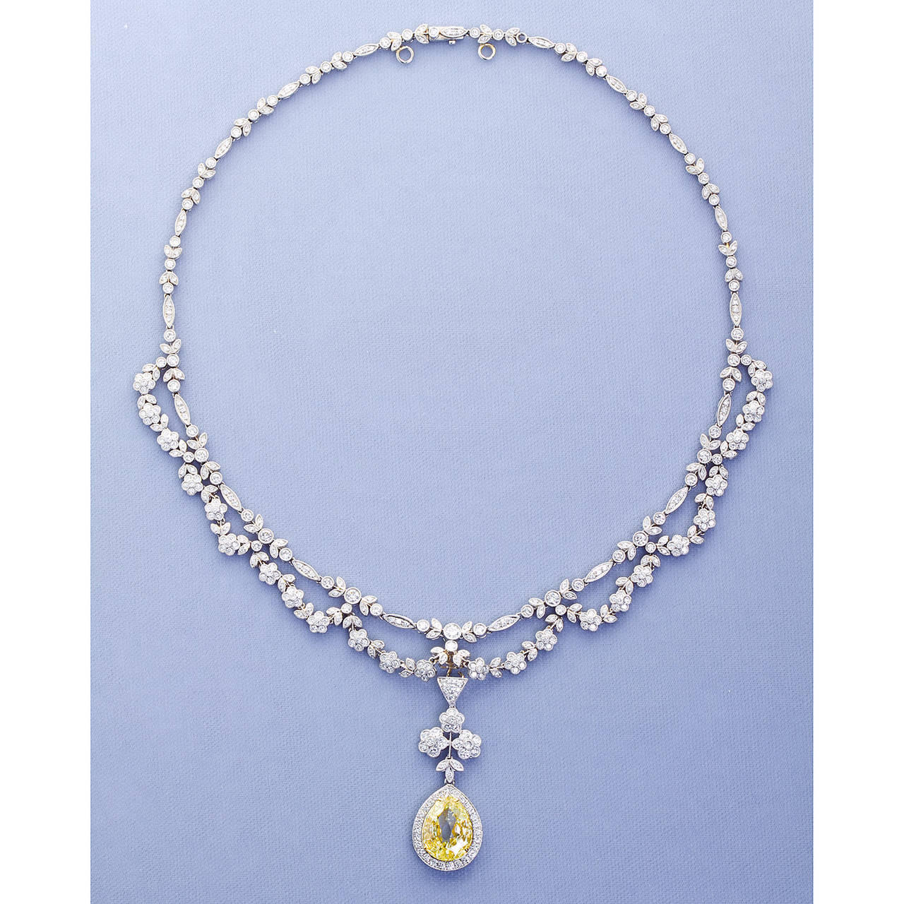 A diamond in platinum festoon style drape necklace circa 1920s with a modified pear shape natural fancy yellow 5.06 carat diamond pendant. Necklace contains approx. 6.50 carat total diamonds. 5.06 carat pear shape accompanied by GIA report stating