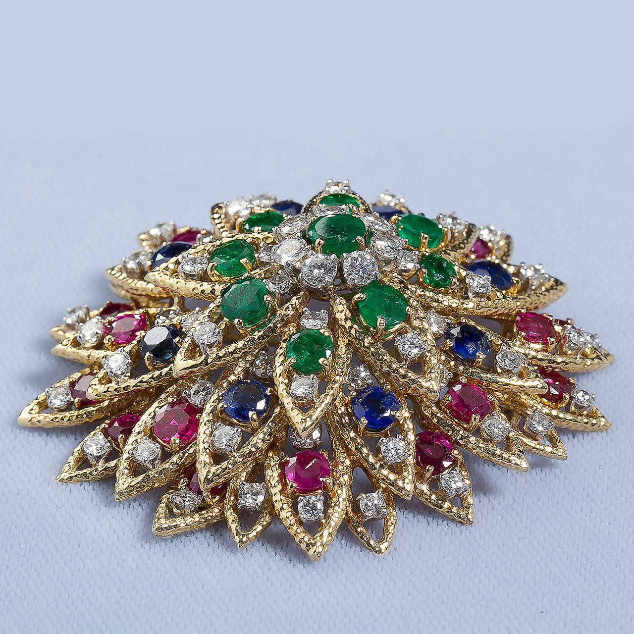 A diamond and multi-gem in 18k gold stylized elaborate brooch by David Webb. Contains round brilliant diamonds, sapphires, rubies and emeralds. Measures approx. 2-1/2 inches wide.  No. 6528