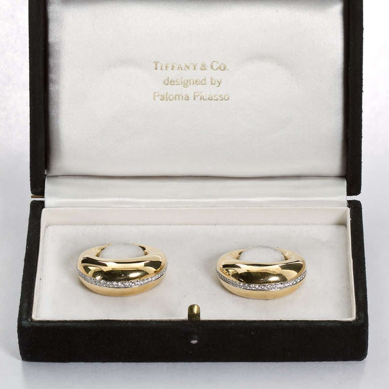 A unique horseshoe styled pair of 18k yellow gold earrings or rings with a diamond stripe across the top. By Paloma Picasso for Tiffany & Co.  No. 5815