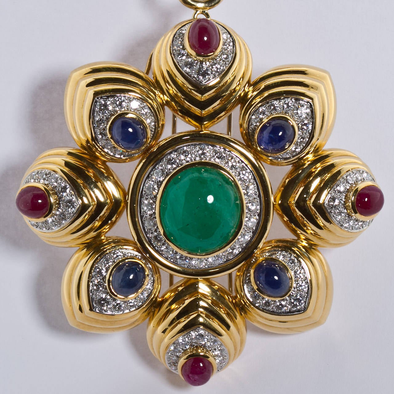 A substantial 18k yellow gold eight pointed combination brooch/pendant with a large center cabochon emerald, and four each of smaller cabochon blue  sapphires and cabochon rubies.  Brilliant round diamond pavé style borders surround each gem. By