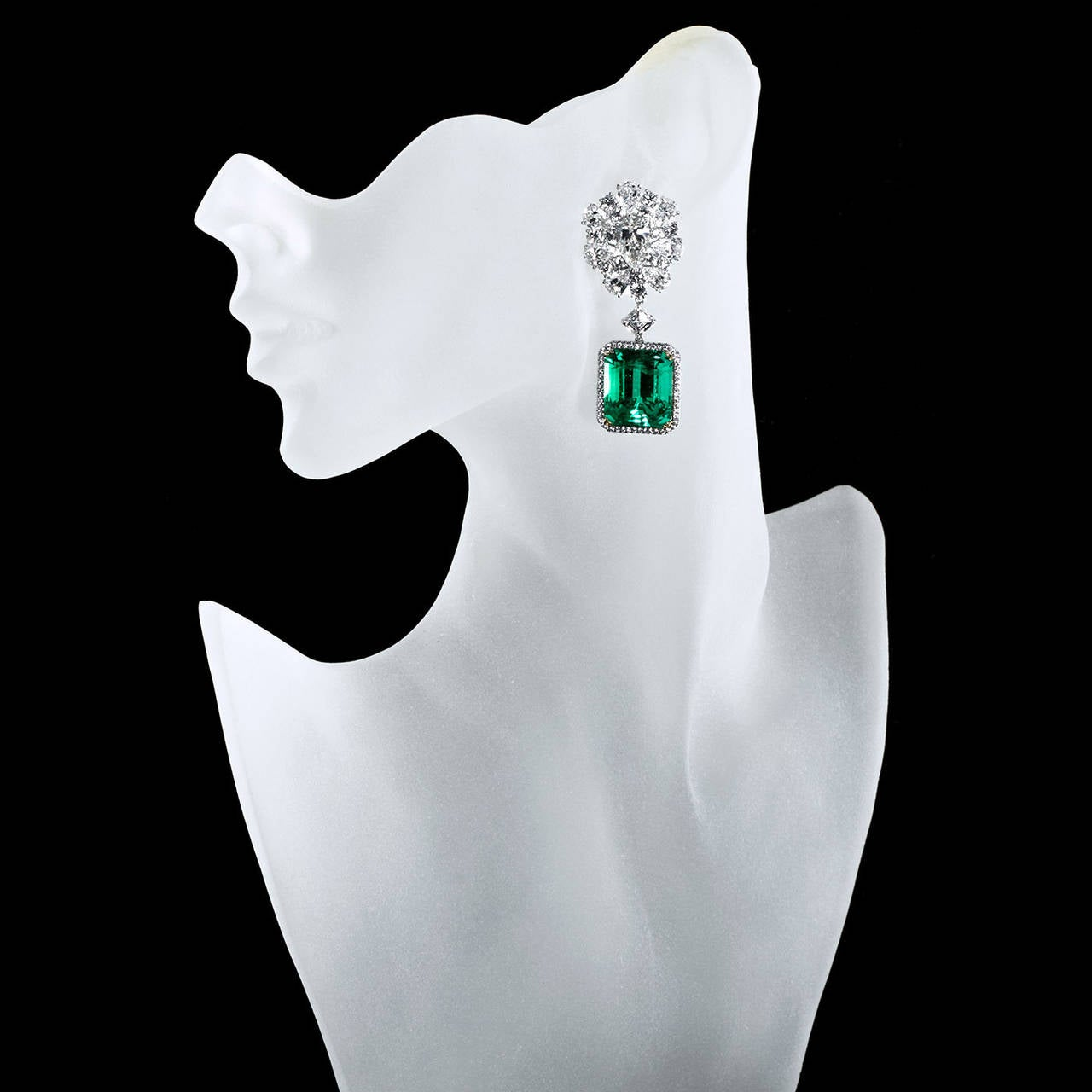 An exquisite pair of diamond and emerald earrings. Earring tops are formed of a cluster of two large pear shape diamonds in the center with additional pear and round brilliant cut diamonds.  The pair of 45 carat total natural Colombian emerald