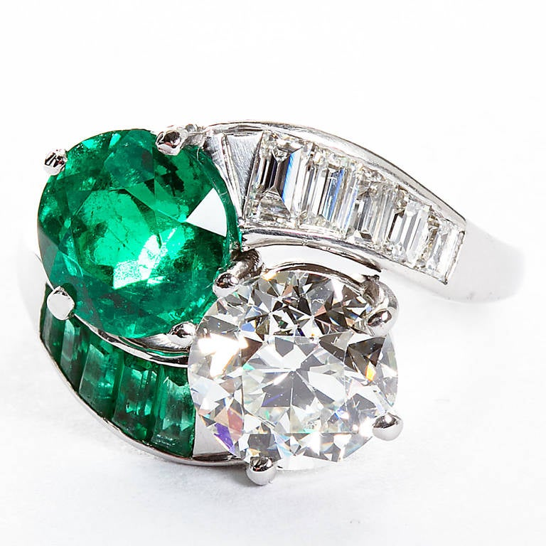 Two gems joining as one. A vintage ring containing a 1.93ct round cut Colombian Emerald and a 2.04ct old European cut near colorless diamond of I color SI1 clarity set in platinum with calibrated emerald and diamond baguettes adorning the sides.