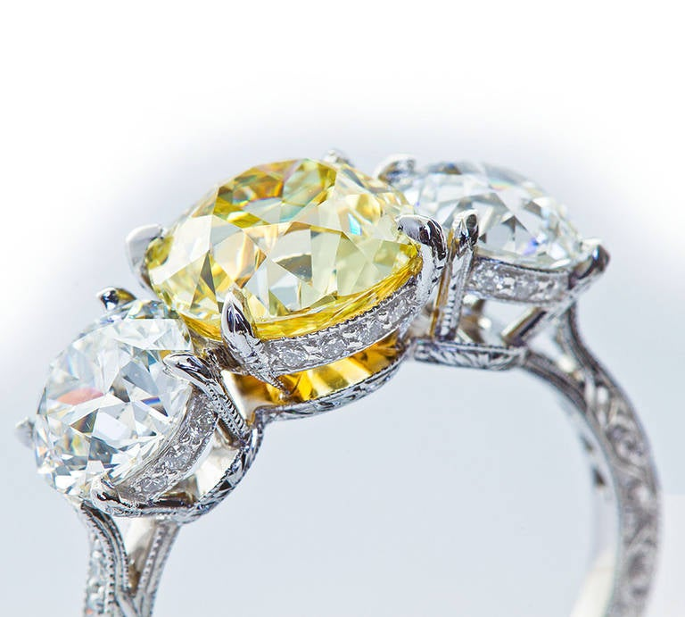 An exquisitely crafted antique platinum and 18 karat yellow gold three-stone ring with filigree ring sides and very fine milgrain and pave diamond basket settings. Center stone Old Mine brilliant cut 2.72 carat Fancy Yellow color SI1 clarity