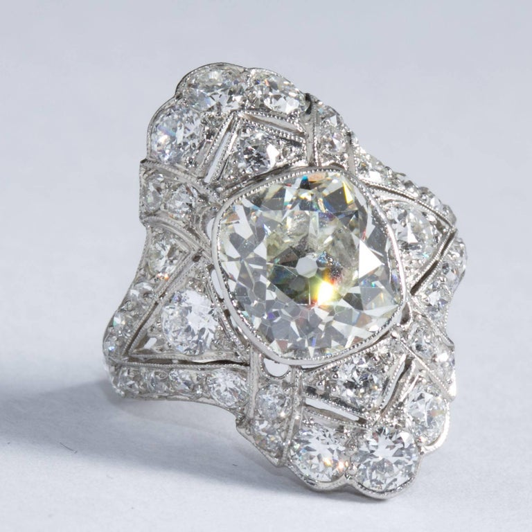 A very fine original navetté style Art Deco ring inlaid with fine diamonds and filigree edging set with a rare center antique cushion cut diamond weighing approximately 4.60 carats. Diamond is graded according to the Gemological Institute of America