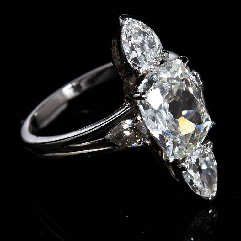 A unique three stone ring set with a center 3.02 carat cushion cut G VVS1 and two pear shape side stones.  No. 5980